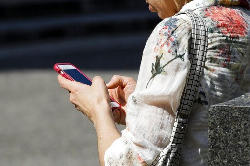 (AP Photo/Matt Rourke, File). FILE - In this April 8, 2019, file photo, a woman browses her smartphone in Philadelphia. Accidental cuts and bruises to the face, head and neck from cellphones are sending increasing numbers of Americans to the emergency ...