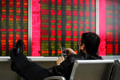(AP Photo/Andy Wong). A man checks stock prices through his smartphone at a brokerage house in Beijing, Friday, Dec. 6, 2019. Shares swung higher in Asia on Friday after a wobbly day of trading on Wall Street as investors awaited a U.S. government jobs...