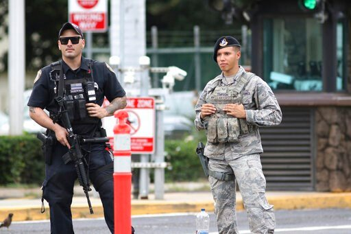 (AP Photo/Caleb Jones). Security stands guard outside the main gate at Joint Base Pearl Harbor-Hickam, in Hawaii, Wednesday, Dec. 4, 2019. A shooting at Pearl Harbor Naval Shipyard in Hawaii left at least one person injured Wednesday, military and hosp...