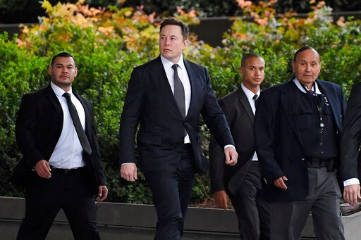 (AP Photo/Mark J. Terrill). Tesla CEO Elon Musk, second from left, arrives at U.S. District Court Wednesday, Dec. 4, 2019, in Los Angeles. Musk is going on trial for his troublesome tweets in a case pitting the billionaire against a British diver he al...