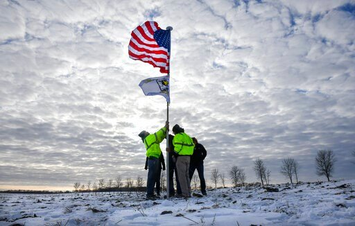 (Dave Schwarz/St. Cloud Times via AP). Members of the Krippner family raise a flag Friday, Dec. 6, 2019, in tribute to victims of a Minnesota National Guard Blackhawk helicopter crash that happened on their land near Kimball, Minn. Three soldiers were ...
