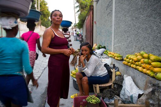(AP Photo/Dieu Nalio Chery). In this Nov. 27, 2019 photo, Wadlande Pierre, right, talks on her mobile phone as she helps her mother, Vanlancia Julien, center, at their fruit and vegetable stand on a sidewalk in Delmas, a district of in Port-au-Prince, ...