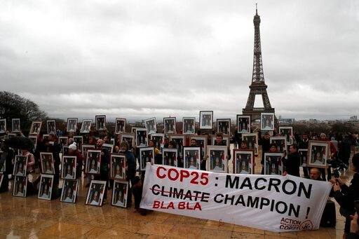 (AP Photo/Francois Mori). A hundred activists hold portraits of President Emmanuel Macron to urge France to take action during the U.N. COP 25 climate talks in Madrid, during a gathering at Place du Trocadero facing the Eiffel Tower in Paris, Sunday, D...