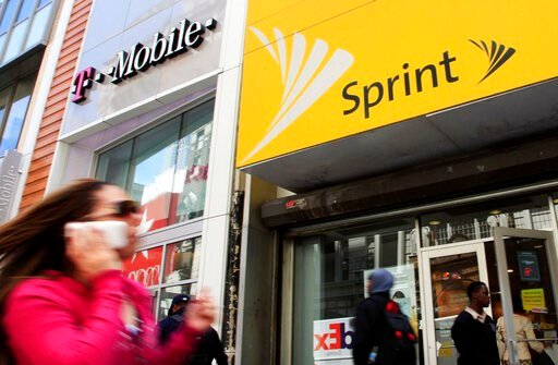 (AP Photo/Mark Lennihan, File). FILE - In this April 27, 2010 file photo, a woman using a cell phone walks past T-Mobile and Sprint stores in New York. T-Mobile, in its attempt to buy Sprint for $26.5 billion, shrinking the major wireless companies to ...