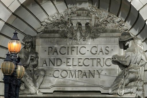 (AP Photo/Jeff Chiu). FILE - In this Oct. 10, 2019, file photo, a Pacific Gas & Electric sign is shown outside of a PG&E building in San Francisco. Pacific Gas and Electric says it has reached a $13.5 billion settlement that will resolve all ma...