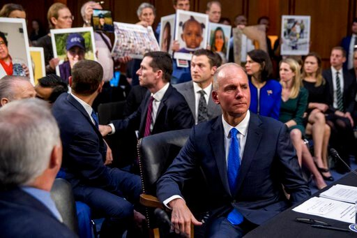 (AP Photo/Andrew Harnik, FIle). FILE - In this Oct. 29, 2019, file photo Boeing Company President and Chief Executive Officer Dennis Muilenburg, right foreground, watches as family members hold up photographs of those killed in the Ethiopian Airlines F...