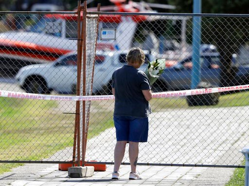 (AP Photo/Mark Baker). A woman places a bouquet of flowers at the fence of a restricted area on the waterfront in Whakatane, New Zealand, Tuesday, Dec. 10, 2019. A volcanic island in New Zealand erupted Monday in a tower of ash and steam while dozens o...