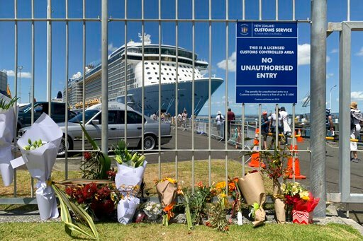 (AP Photo/Nick Perry). Flowers are laid on makeshift memorial is seen in front of cruise ship Ovation of the Seas, in Tauranga, New Zealand, Tuesday, Dec. 10, 2019. A volcanic island in New Zealand erupted Monday Dec. 9 in a tower of ash and steam whil...