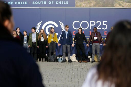 (AP Photo/Andrea Comas). Young activists from the 'Fridays For Future' climate protest Movement form a human chain at the COP25 Climate summit in Madrid, Spain, Monday, Dec. 9, 2019. A global U.N.sponsored climate change conference is taking place in M...