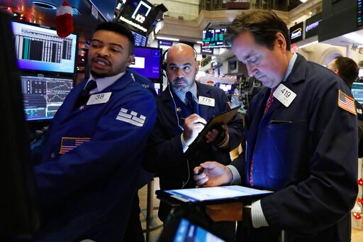 (AP Photo/Richard Drew, File). FILE - In this Dec. 5, 2019, file photo specialist Christopher Riggs, left, works with traders Fred DeMarco, center and Philip Powers on the floor of the New York Stock Exchange. The U.S. stock market opens at 9:30 a.m. E...