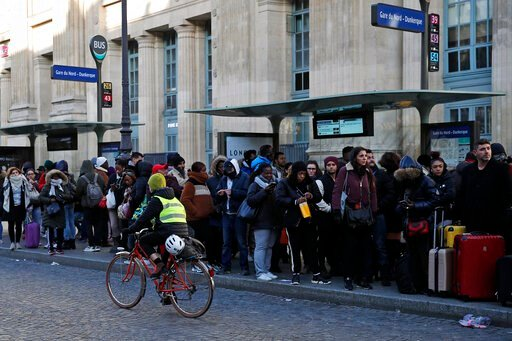 (AP Photo/Francois Mori). A woman rides her bicycle as commuters wait for a bus at Gare du Nord Station, in Paris, Tuesday, Dec. 10, 2019. Only about a fifth of French trains ran normally Tuesday, frustrating tourists finding empty train stations, and ...