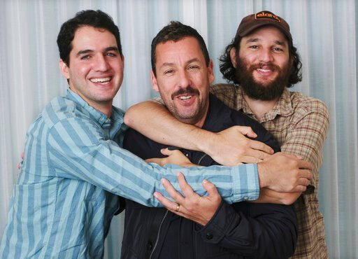 "(Photo by Chris Pizzello/Invision/AP). This Sept. 9, 2019 photo shows Adam Sandler, center, star of the film ""Uncut Gems,"" posing for a portrait with co-directors Benny Safdie, left, and his brother Josh at the St. Regis Hotel during the Toronto Intern..."