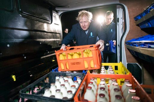 (Stefan Rousseau/PA via AP). Britain's Prime Minister Boris Johnson loads a crate into a milk delivery van during a visit to Greenside Farm Business Park, as he campaigns for votes on the last day of campaigning ahead of Thursday's General Election, in...