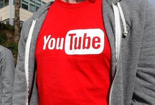 (AP Photo/Jeff Chiu, File). FILE - This April 4, 2018, file photo shows a YouTube logo on a t-shirt worn by a person near a YouTube office building in San Bruno, Calif. YouTube is taking another step to curb hateful and violent speech on its site. The ...
