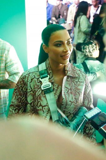 (AP Photo/Brynn Anderson). In this Tuesday, Dec. 3, 2019, photo, actress Kim Kardashian waits for the Christian Dior pre-fall 2020 men's fashion show to start during Miami Art week, in Miami.
