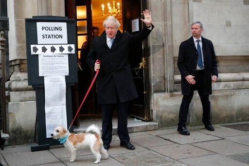 (AP Photo/Frank Augstein). Britain's Prime Minister and Conservative Party leader Boris Johnson with his dog Dilyn as he leaves after voting in the general election at Methodist Central Hall, Westminster, London, Thursday, Dec. 12, 2019. The general el...