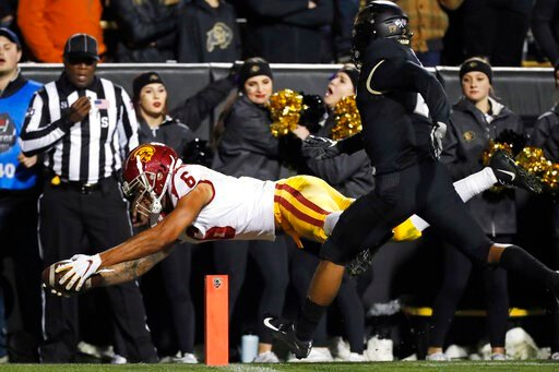 (AP Photo/David Zalubowski, File). FILE - In this Oct. 25, 2019, file photo, Southern California wide receiver Michael Pittman Jr. dives into the end zone to score a touchdown after pulling in a pass in front of Colorado safety Mikial Onu during the se...