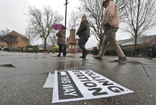 (AP Photo/Frank Augstein). A polling station signpost lies on the pavement as voters approach a polling station in Twickenham, England, Thursday, Dec. 12, 2019. British voters are deciding who they want to resolve the Brexit conundrum in an election se...