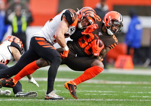(AP Photo/Ron Schwane). Cincinnati Bengals defensive back Clayton Fejedelem (42) tackles Cleveland Browns wide receiver Jarvis Landry (80) during the first half of an NFL football game, Sunday, Dec. 8, 2019, in Cleveland.