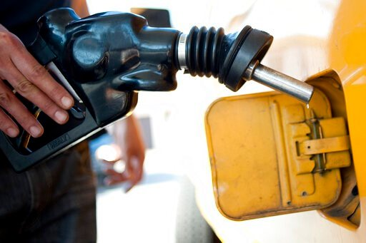 (AP Photo/Grant Hindsley, File). FILE - In this Aug. 10, 2012 file photo a customer pumps gas into his dual-tank pickup truck at a 76 gas station in Los Angeles. California regulators will hold a public hearing on Thursday, Dec. 12, 2019 about whether ...