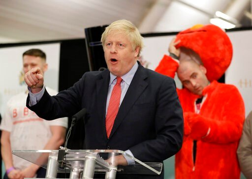 (AP Photo/Kirsty Wigglesworth). Bobby Smith, a political and fathers' rights activist and founder and leader of the 'Give Me Back Elmo' party watches as Britain's Prime Minister and Conservative Party leader Boris Johnson speaks after the Uxbridge and ...
