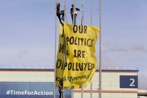 (AP Photo/Paul White). Greenpeace activists display a banner outside the COP25 climate talks congress in Madrid, Spain, Friday, Dec. 13, 2019. The United Nations Secretary-General has warned that failure to tackle global warming could result in economi...