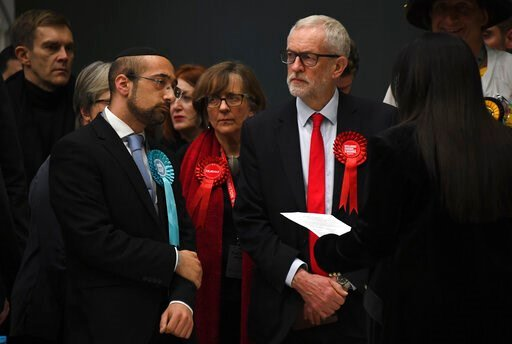 (AP Photo/Alberto Pezzali). British opposition Labour Party leader Jeremy Corbyn, right,  waits for the declaration of his seat in the 2019 general election in Islington, London, Friday, Dec. 13, 2019. The first handful of results to be declared in Bri...