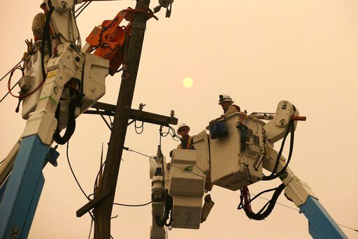 (AP Photo/Rich Pedroncelli, File). FILE - In this Nov. 9, 2018 file photo, Pacific Gas & Electric crews work to restore power lines in Paradise, Calif.  California Gov. Gavin Newsom has rejected Friday, Dec. 13, 2019, a bankruptcy reorganization pl...