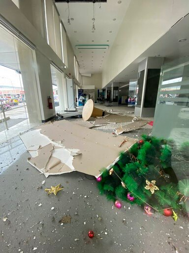(Philippine Red Cross via AP). In this photo provided by the Philippine Red Cross, a Christmas tree and other debris lie on the ground inside a building after a strong earthquake shook Digos, Davao del Sur province, southern Philippines on Sunday Dec. ...