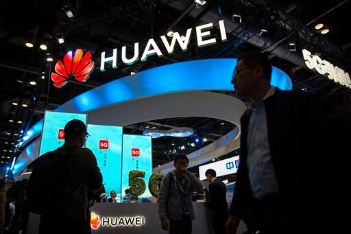 (AP Photo/Mark Schiefelbein, File). FILE - In this Thursday, Oct. 31, 2019 file photo, attendees walk past a display for 5G services from Chinese technology firm Huawei at the PT Expo in Beijing. Norway's biggest wireless carrier, Telenor, on Friday De...