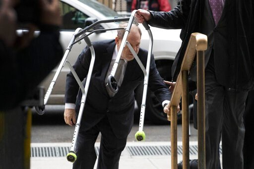 (AP Photo/Mark Lennihan). Harvey Weinstein walks up the steps at a Manhattan courthouse as an assistant carries his walker as he arrives for jury selection in his rape trial, Monday, Jan. 13, 2020, in New York.