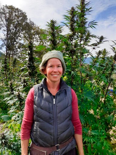 (Rosales CBD via AP). In this undated photo provided by Rosales CBD, Dove Oldham poses in front of a hemp plant growing at Madrona Family Farm in Grants Pass, Oregon. Oldham, who sells hemp-derived CBD products under the name Rosales CBD, says she is c...