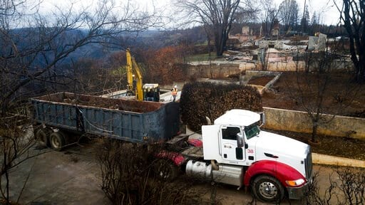 (AP Photo/Noah Berger, File). FILE - In this Feb. 8, 2019, file photo, an excavator loads debris onto a truck while clearing a property burned by the Camp Fire in Paradise, Calif. A $13.5 billion settlement covering most of the losses from a series of ...