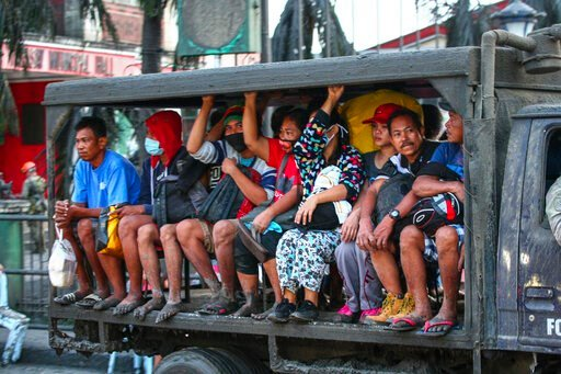 (AP Photo/Gerrard Carreon). Residents are evacuated as heavy ash and debris from the Taal volcano eruption continues to fall on their town in Talisay, Batangas, southern Philippines on Monday, Jan. 13, 2020. Red-hot lava gushed out of a volcano near th...