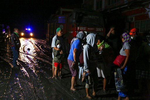 (AP Photo/Gerrard Carreon). Residents wait to be evacuated as heavy ash and debris from the Taal volcano eruption cover their town in Talisay, Batangas, southern Philippines, Monday, Jan. 13, 2020. Red-hot lava gushed out of a volcano near the Philippi...