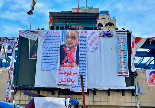 """(AP Photo/Khalid Mohammed). In this Monday, Jan. 13, 2020 photo, a poster with a defaced picture of Iraqi acting Prime Minister Adil Abdul-Mahdi, and Arabic that reads, """"Your return is rejected, loser,"""" hangs in Tahrir Square, in Baghdad, Iraq. Mass pr..."""