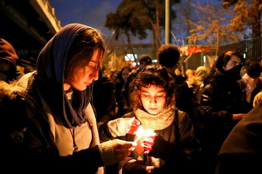 (AP Photo/Ebrahim Noroozi). People gather for a candlelight vigil to remember the victims of the Ukraine plane crash, at the gate of Amri Kabir University that some of the victims of the crash were former students of, in Tehran, Iran, Saturday, Jan. 11...