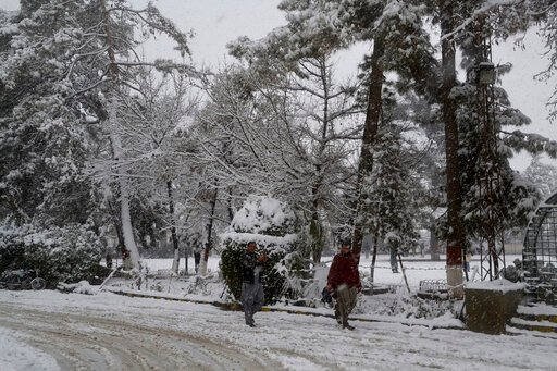 (AP Photo/Arshad Butt). In this Sunday, Jan. 12, 2020, photo, people walk on a road during heavy snow fall in Quetta, capital of Pakistan's southwestern Baluchistan province. Much of the damage was caused in Pakistan's southwestern Baluchistan province...