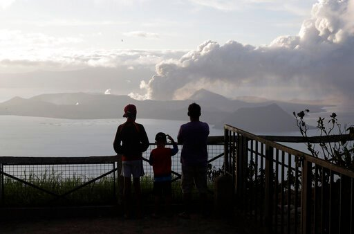 (AP Photo/Aaron Favila). People watch from Tagaytay, Cavite province, south of Manila, as Taal Volcano continues to spew ash on Tuesday, Jan. 14, 2020. Thousands of people fled the area through heavy ash as experts warned that the eruption could get wo...