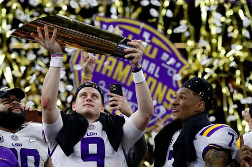 (AP Photo/Sue Ogrocki). LSU quarterback Joe Burrow holds the trophy as safety Grant Delpit looks on after a NCAA College Football Playoff national championship game against Clemson, Monday, Jan. 13, 2020, in New Orleans. LSU won 42-25.