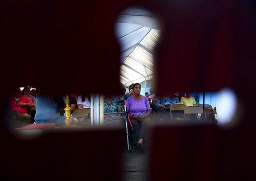 (AP Photo/Carlos Giusti). Seen through the cut-out shape of a cross on a priest's chair, a woman attends an outdoor Mass under a tent set up near the Immaculate Concepcion Catholic Church, which sustained earthquake-related damaged earlier in the week,...