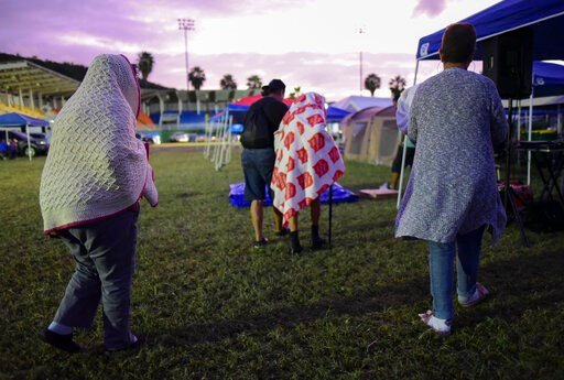 (AP Photo/Carlos Giusti). People get up after spending the night in a baseball stadium amid aftershocks and without electricity after the 6.4 magnitude earthquake in Guayanilla, Puerto Rico, at sunrise Friday, Jan. 10, 2020. Hundreds of thousands of Pu...