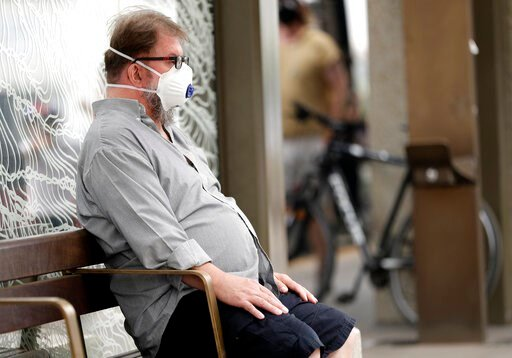 (AP Photo/Mark Baker, File). FILE - In this Jan. 2, 2020, file photo, a commuter wears a mask as smoke shrouds the Australian capital of Canberra, Australia. It's an unprecedented dilemma for Australians accustomed to blue skies and sunny days that has...