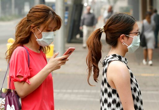 (AP Photo/Mark Baker, File). FILE - In this Jan. 2, 2020, file photo, pedestrians wear masks as smoke shrouds the Australian capital of Canberra, Australia. It's an unprecedented dilemma for Australians accustomed to blue skies and sunny days that has ...