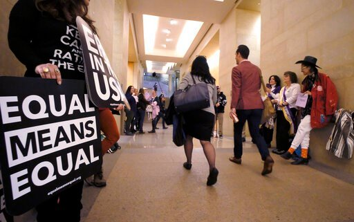 (Bob Brown/Richmond Times-Dispatch via AP). An Equal Rights Amendment supporters yell encouragement to two legislators as they walk down a hallway inside the state Capitol in Richmond, Va., Tuesday, Jan. 14, 2020. A House committee approved a resolutio...