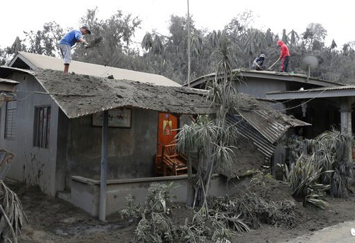 (AP Photo/Aaron Favila). In this Jan. 14, 2020, photo, residents clean their roofs from volcanic ash in Laurel, Batangas province, southern Philippines, as Taal volcano continues to spew ash. So far no one has been reported killed in the eruption, but ...