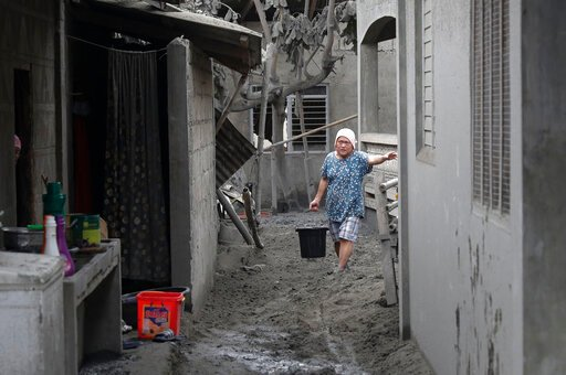 (AP Photo/Aaron Favila). In this Jan. 14, 2020, photo, a resident fetches water at their volcanic ash covered village in Laurel, Batangas province, southern Philippines, as Taal volcano continues to spew ash. So far no one has been reported killed in t...