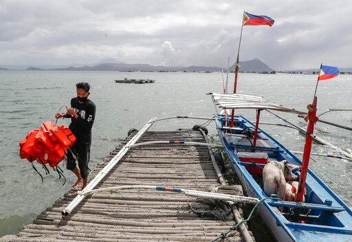 (AP Photo/Aaron Favila). In this Jan. 14, 2020, photo, Christian Morales carries life vests beside his pigs which they rescued across the lake in Talisay, Batangas province, southern Philippines, as Taal volcano continues to spew ash. So far no one has...