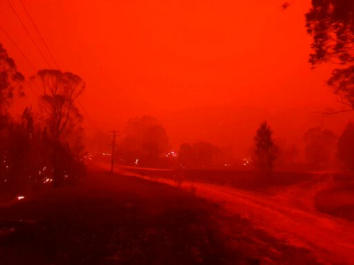 (AP Photo/Siobhan Threlfall). In this Dec. 31, 2019, photo provided by Siobhan Threlfall, fire and thick smoke remains the village of Nerrigundah, Australia. The tiny village has been among the hardest hit by Australia's devastating wildfires, with abo...