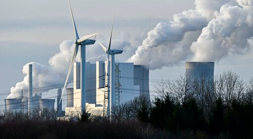 (AP Photo/Martin Meissner). The RWE Niederaussem lignite-fired power station releases steam, behind two renewable energy producing wind turbines in Bergheim, Germany, Monday, Jan. 13, 2020. Germany plans an entirely coal phase out and to shut down all ...